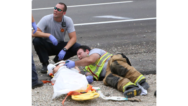 Fire-medic watches a movie on his phone with a child injured in a wreck.